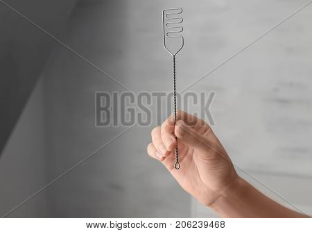Hand of woman with logopedic probe for speech correction indoors