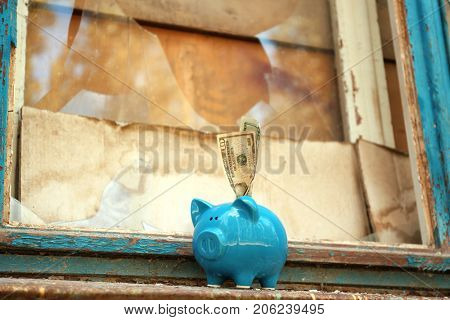 Old window and piggy bank with money. Window repair concept
