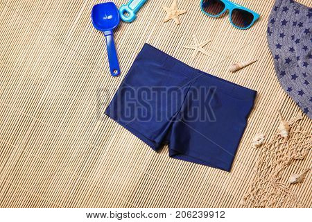 Set of boy's beach accessories on wicker background