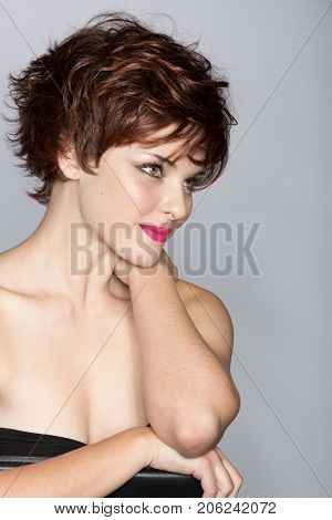 beautiful young woman with short brown pixie haircut wears red pink lipstick, sitting on studio background