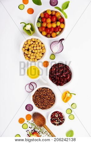 Selection of legumes spices herbs and organic vegetables. Ingredients for cooking. Food background on white. Top view copy space.
