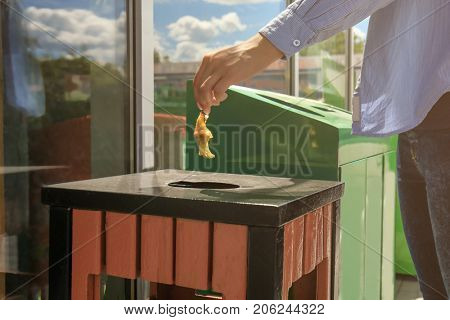 Woman throwing apple stump into litter bin outdoors