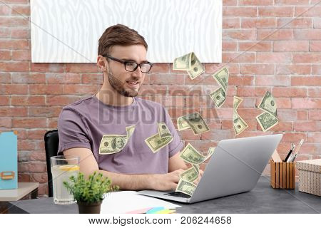 Money flying out of laptop while man using it at table in office