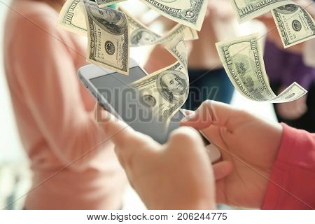 Money flying out of phone while woman using it on blurred background