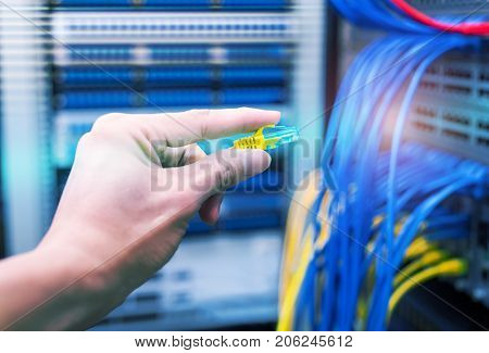administrator holding network cables connected to servers