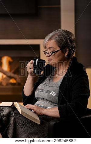 Mature woman sitting at fireplace on a winter day. reading book and drinking tea.