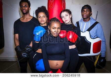 Portrait of four young determined boxers and their experienced boxing trainer looking at camera
