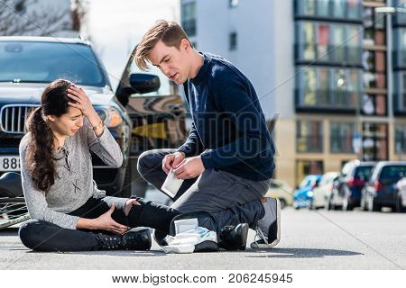 Young male driver using a sterile adhesive bandage from his first aid kit to help an injured female bicyclist on the street