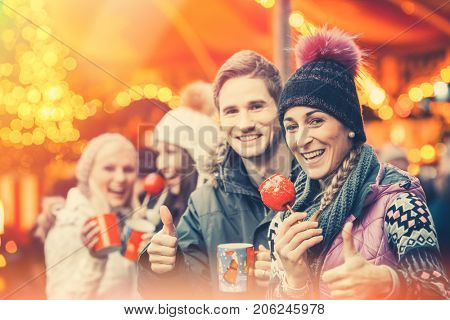 Friends drinking mulled wine and eating crystalized appels on German Christmas Market