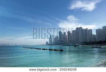 Residential and commercial buildings and skyline at Dubai Marina. A view from a beach.