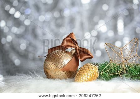 Beautiful composition with Christmas decorations and brunches of fir tree on soft plaid against blurred background