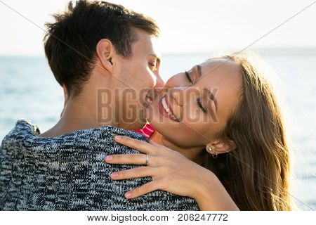 Young couple hugging on the beach near the sea