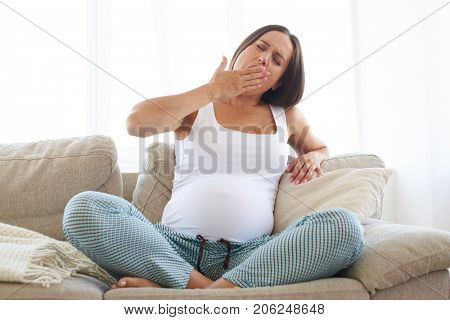 Closeup of tired pregnant woman sitting on sofa and yawning