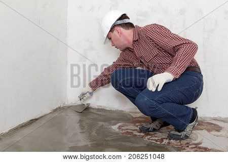 Construction worker spreading concrete during flooring installation