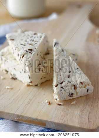 Cottage cheese with cumin on a rustic table