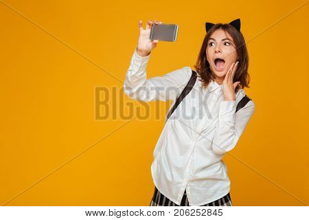 Surprised teenage schoolgirl in uniform with backpack taking a selfie while standing isolated over orange background