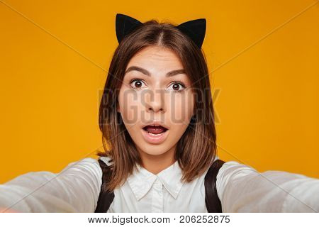 Close up portrait of a surprised teenage schoolgirl in uniform with backpack taking a selfie while standing and looking at camera isolated over orange background
