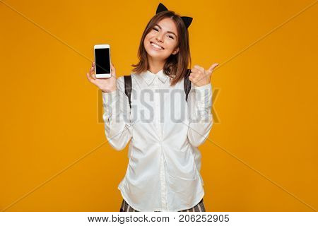 Smiling teenage schoolgirl in uniform with backpack holding blank screen mobile phone and showing thumbs up gesture isolated over orange background