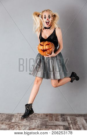 Full length portrait of an excited crazy blonde woman in halloween clown make-up and blood streaks holding curved pumpkin and jumping isolated over gray background