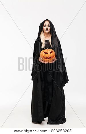 Full length portrait of a young blonde woman in halloween make-up and black robe holding curved pumpkin isolated over white background