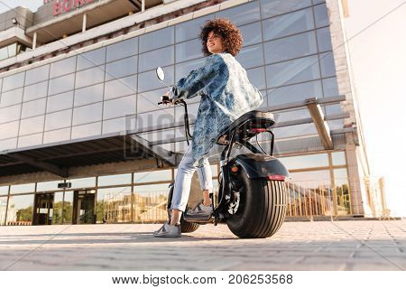 Full length view from below of smiling curly woman sitting on modern motorbike outdoors and looking away