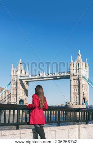 London people lifestyle city tourist woman looking at view of Tower Bridge in red trench coat. Bridge. Stylish elegant lady fashion girl walking enjoying urban modern life.