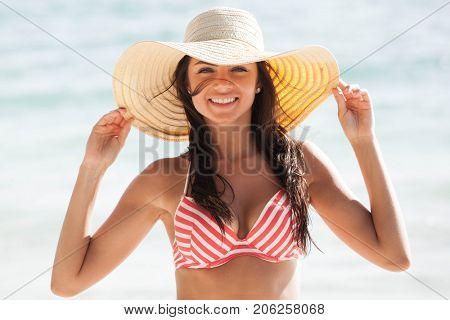 Beautiful young woman in sexy bikini and sunhat standing at sea beach