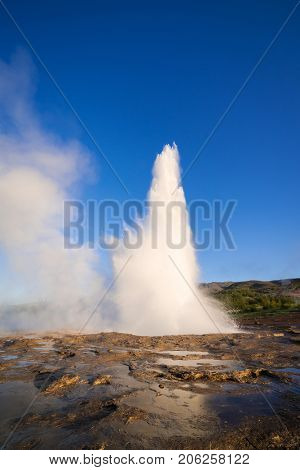 Eruption of the Geysir geyser. Valley Haukadalur, Iceland. Golden Ring Tourist Attraction. Sunny day with clear blue sky. Amazing nature