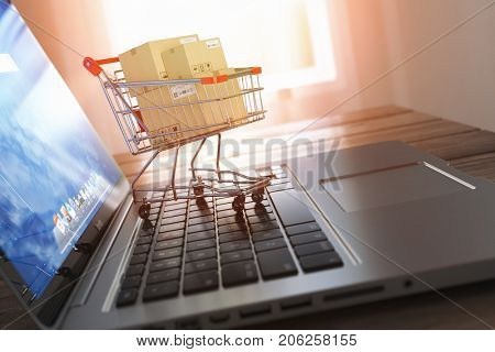 Shopping online and e-commerce. Laptop and shopping cart with boxes on laptop keyboard, 3d illustration