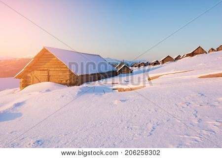 Winter landscape in a mountain village. Wooden houses and huts in the snow. Sunny morning