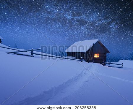 Night with stars. Christmas landscape. Wooden house in the mountain village