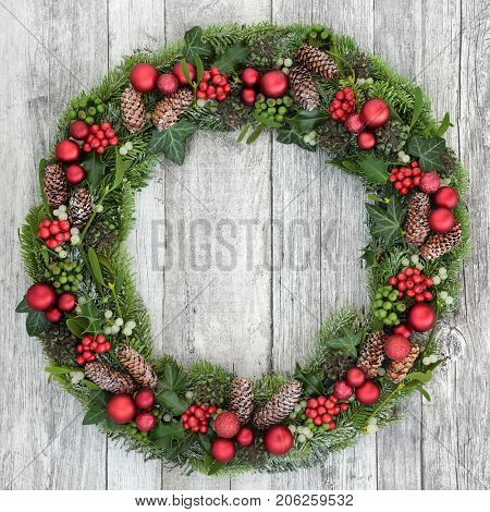 Christmas wreath decoration with red baubles, holly, mistletoe, pine cones, juniper fir, blue spruce, cedar, and ivy on distressed white wood front door background.