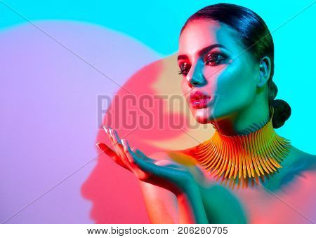 High Fashion model woman portrait in colorful bright lights, beautiful party girl with trendy make-up, manicure, haircut. Pointing hand, advertising gesture over colourful vivid background