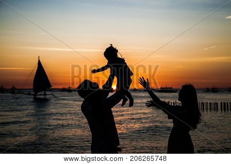 Happy family - silhouette of father tossing baby girl and mother on sunset sea . Philiphines.
