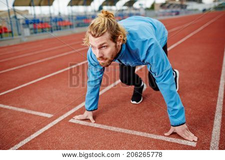 Determined young man in sportswear waiting for start signal during run competition