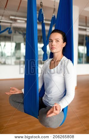 Serene woman in activewear sitting in pose of lotus in blue hammock during aero-yoga training