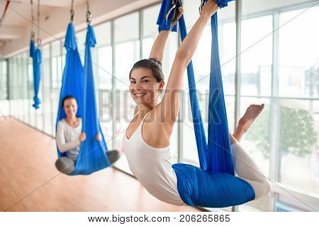 Happy female hanging and swinging in hammock during aero yoga workout