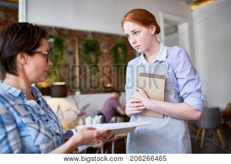Displeased client of cafe complaining waitress about menu or bad service