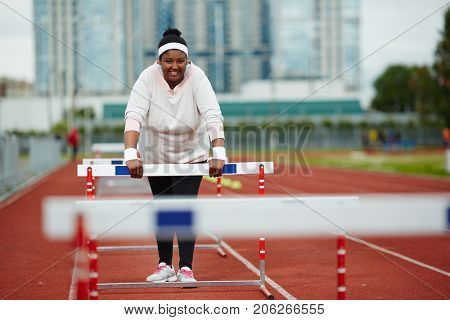 Happy plus-sized woman in activewear leaning forward on hurdle during training on stadium