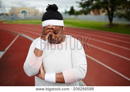 Tired chubby woman in activewear touching her forehead after training