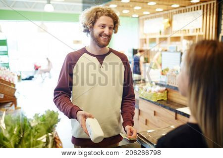 Happy young man showing bottle of milk to cashier and going to pay by cash