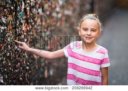 Girl putting gum on the wall in bubble gum alley
