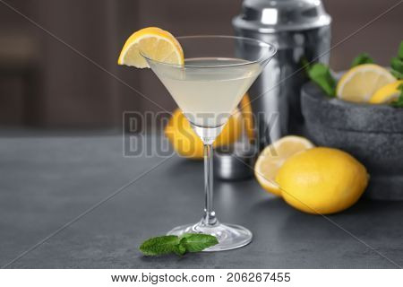 Glass with tasty lemon drop martini cocktail on table