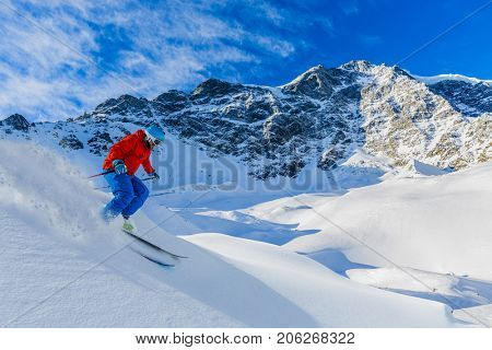 Mountaineer alpine skiing  along a snowy ridge. In background blue sky and shiny sun and Zebru, Ortler in South Tirol, Italy.  Adventure winter extreme sport.