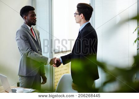 Confident young entrepreneurs standing at modern boardroom and shaking hands after successful completion of negotiations, profile view