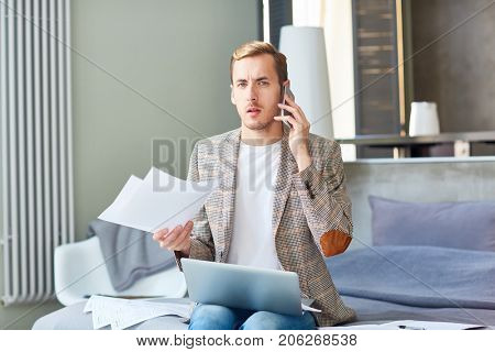 Dissatisfied handsome freelancer looking at camera while sitting on cozy bed and talking to his client on mobile phone, interior of modern studio apartment on background