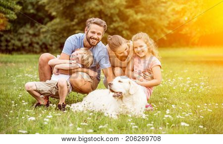 Happy family with children and dog in summer in the garden