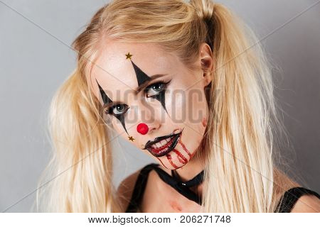 Close up portrait of carefree blonde woman in halloween make up looking at the camera over gray background