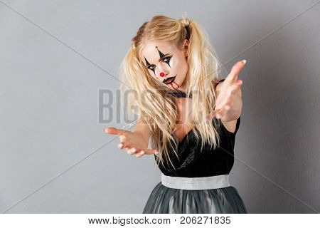 Young blonde woman in halloween make up extends her hands and looking at the camera over gray background