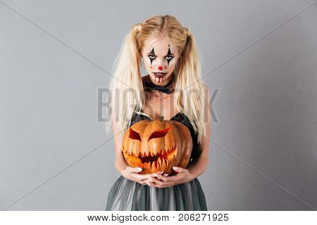 Frightening blonde woman in halloween make up holding carved pumpkin and looking at the camera over gray background